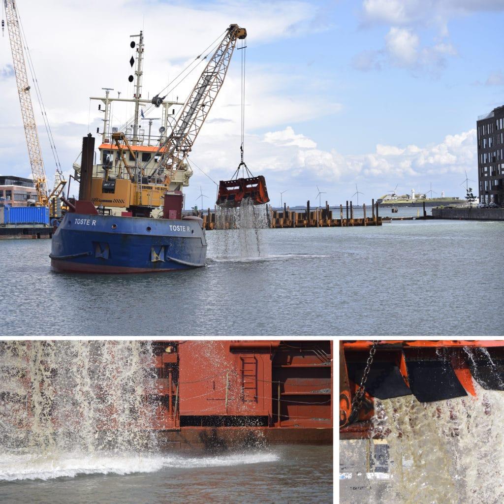 Oprensning af sediment i Kronløbsbassinet, hvor Kronløbsøen skal bygges. Et skib udstyret med kran og en særlig grab sejler ind i bassinet og fylder lastrummet med noget, der mest af alt ligner slam.
