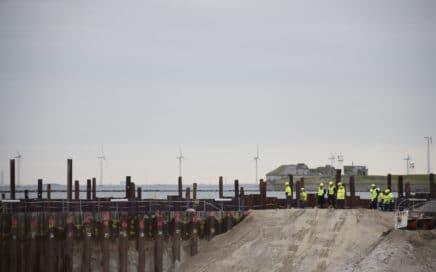 Sikkerhedsklædte mennesker betragter byggegruppen v Kronløbsøens byggeplads.